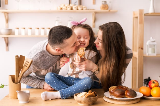 child happily eats with parents in the kitchen