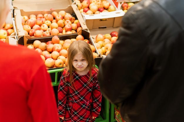 little girl looks angrily towards mom and dad while standing beside a supermarket food stall
