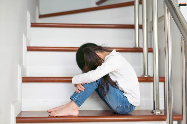 an upset child with her head and hands on her knees sitting in the stair