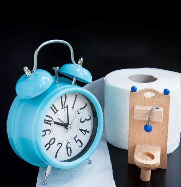 Wooden toy toilet, toilet paper and alarm clock on black background