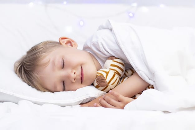 Charming little white boy sleeps in bed. hugs a soft toy