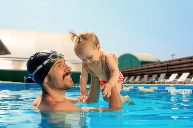 dad carrying toddler in the swimming pool