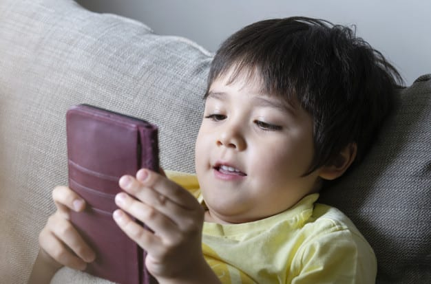 Close up Cute boy watching cartoons on mobile phone,Preschool kid with smiling face lying on sofaChild typing on cell phone while relaxing