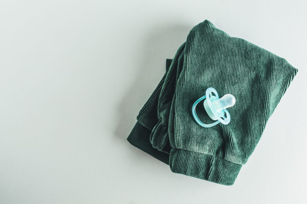 Baby care or baby shower concept. Flat Lay. Newborn or baby cloth and nipple.