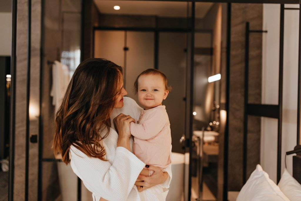 Baby in pink jumpsuit smiles sweetly while his mom talks to him. Long-haired lady in white bathrobe playing with child on background of bathroom