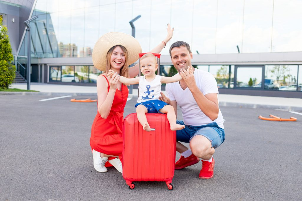 happy family mom, dad and child at the airport with a red suitcase goes on a trip or vacation