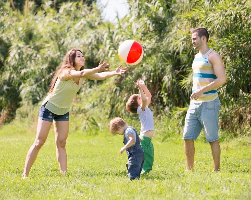 Smiling parents with children playing in park at sunny day