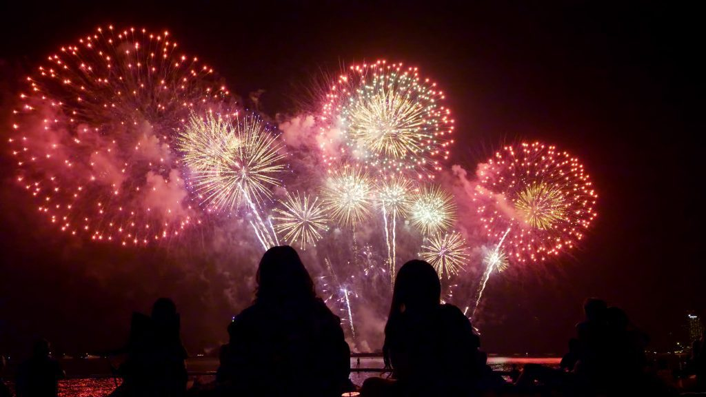 People watching beautiful fireworks together by the sea at night.