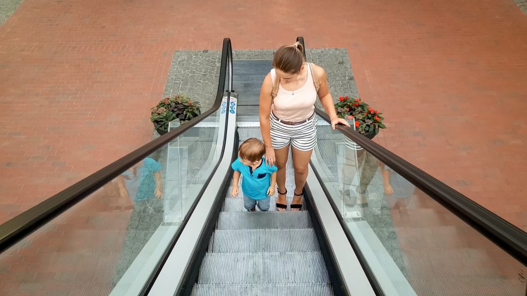Image of young mother holding her little son by hand while riding on the escalator at shopping mall