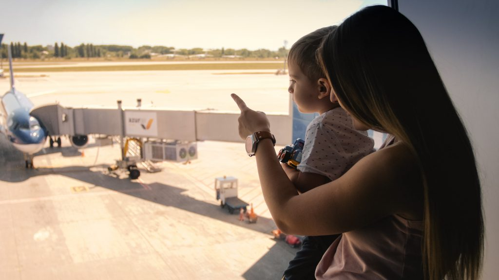 Toned image of young mother showing airplanes on runway at airport to her little son.